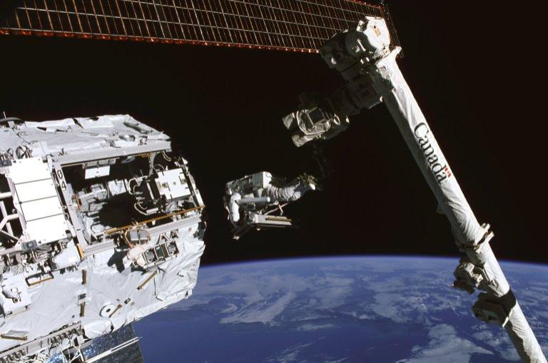 Morin handles a keel pin and is moved by the SSRMS during the second EVA of STS-110