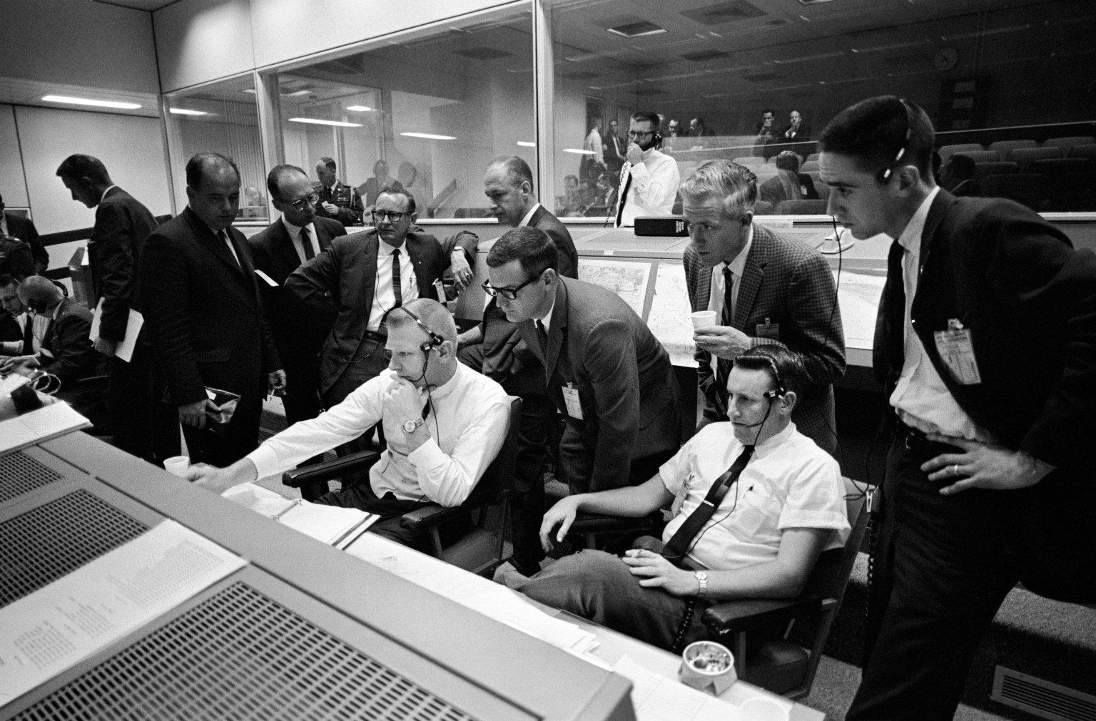 Personnel in Mission Control discuss the postponement of the Gemini 9 mission