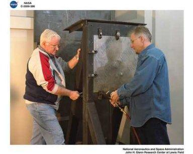 WORKERS SETTING A TEST IN THE BALLISTIC IMPACT LABORATORY WITH TOM MONAHAN AND GRANT BROWN