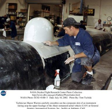 Technician Shawn Warren carefully smoothes out the composite skin of an instrument fairing atop the