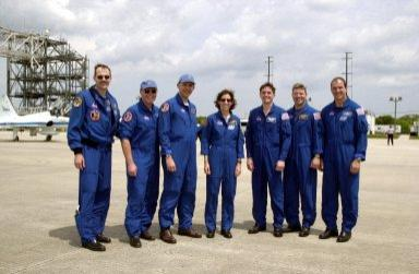 """KENNEDY SPACE CENTER, FLA. -- The STS-110 crew poses for a photo after landing at the KSC Shuttle Landing Facility. Standing left to right are Mission Specialists Steven Smith, Jerry Ross, Lee Morin, Ellen Ocho and Rex Walheim; Pilot Stephen Frick; and Commander Michael Bloomfield. Mission STS-110 is the 13th assembly flight to the International Space Station. During four planned spacewalks, crew members will install the S0 Integrated Truss Structure (ITS), centerpiece of the orbiting International Space Station (ISS), at the center of the 10-truss, girderlike structure that will ultimately extend the length of a football field on the ISS. The S0 truss will be attached to the U.S. Lab, """"Destiny,"""" on the 11-day mission"""
