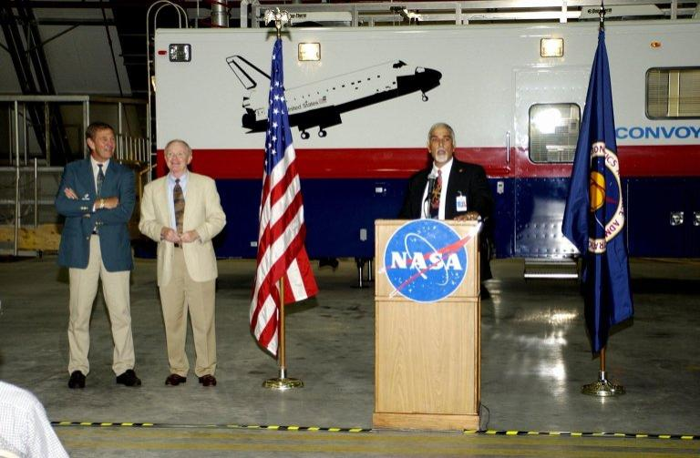 KENNEDY SPACE CENTER, FLA. -- During a commissioning ceremony for the new Convoy Command Vehicle (background), Tony Shibly, project manager, United Space Alliance, offers a few remarks to guests. At left are USA Chief Operating Officer Mike McCulley and Center Director Roy Bridges Jr. The new 40-foot vehicle is replacing a 15-year old model, and will be used following Shuttle landings as the prime vehicle to control critical communications between the orbiter, the crew and the Launch Control Center, to monitor the health of the Shuttle Orbiter systems and to direct convoy operations at the Shuttle Landing Facility. Upgrades and high-tech features incorporated into the design and development of this vehicle make it more reliable and efficient for the convoy crew. Seating capacity was increased from 4 to 12, and video recorders and television monitors were added to provide the convoy team with the maximum amount of visual information