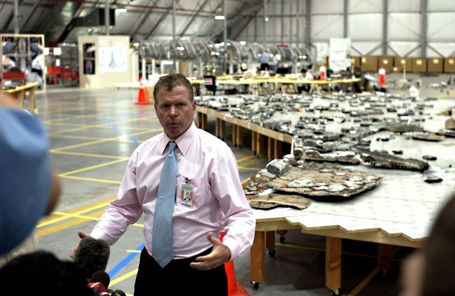 KENNEDY SPACE CENTER, FLA. - U.S. Representative Tom Feeney talks to the media after accompanying Adm. Harold Gehman and the Columbia Investigation Accident Board on their visit to the RLV Hangar. Recovery efforts as of May 5 included 82,500 pieces of debris weighing 84,800 pounds, almost 40 percent of the total dry weight of the shuttle. About 25,000 personnel took part, utilizing almost 1.5 million total man-hours in the recovery effort and involving more than 130 federal, state and local agencies. The operation was also supported by more than 270 organizations that included businesses and volunteer groups.