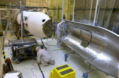 KENNEDY SPACE CENTER, FLA. -- At Vandenberg Air Force Base in California, under the protective clean tent, technicians work on the second half of the fairing to be installed around the AIM spacecraft. The fairing is a molded structure that fits around the spacecraft and forms an aerodynamically smooth nose cone, protecting the spacecraft during launch. Launch will be from a Pegasus XL rocket, carried and released by Orbital Sciences L-1011 jet aircraft. AIM, which stands for Aeronomy of Ice in the Mesosphere, is being prepared for integrated testing and a flight simulation. The AIM spacecraft will fly three instruments designed to study polar mesospheric clouds located at the edge of space, 50 miles above the Earth's surface in the coldest part of the planet's atmosphere. The mission's primary goal is to explain why these clouds form and what has caused them to become brighter and more numerous and appear at lower latitudes in recent years. AIM's results will provide the basis for the study of long-term variability in the mesospheric climate and its relationship to global climate change. Launch is scheduled for April 25.