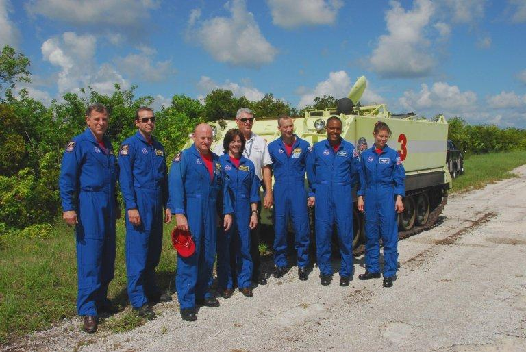 KENNEDY SPACE CENTER, Fla. -- After completing their driving training on the M-113 armored personnel carrier (behind them), the STS-118 crew take a break. From left are Mission Specialists Dave Williams and Rick Mastracchio, Commander Scott Kelly, Mission Specialist Barbara R. Morgan, Pilot Charlie Hobaugh, and Mission Specialists Alvin Drew and Tracy Caldwell. Williams represents the Canadian Space Agency. Morgan joined NASA's Teacher in Space program in 1985 and was selected as an astronaut in 1998. The crew is at Kennedy for the Terminal Countdown Demonstration Test (TCDT), a dress rehearsal for launch. TCDT activities include the M-113 training, payload familiarization, emergency egress training at the pad and a simulated launch countdown. The STS-118 payload aboard Space Shuttle Endeavour includes the S5 truss, a SPACEHAB module and external stowage platform 3. The mission is the 22nd flight to the International Space Station and is targeted for launch on Aug.7. NASA/George Shelton