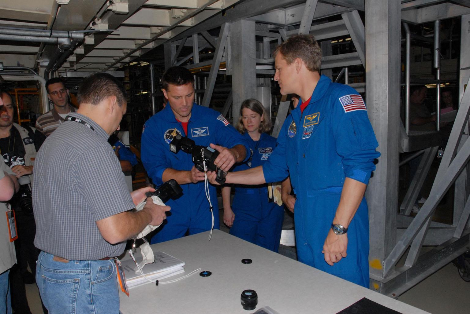 KENNEDY SPACE CENTER, FLA. - The STS-120 crew is at Kennedy for a crew equipment interface test, or CEIT. From left in blue flight suits, STS-120 Mission Specialist Douglas H. Wheelock, Commander Pamela A. Melroy and Mission Specialist Scott E. Parazynski receive instruction in Orbiter Processing Facility bay 3 on the operation of cameras that will fly on their mission. Among the activities standard to a CEIT are harness training, inspection of the thermal protection system and camera operation for planned extravehicular activities, or EVAs. The STS-120 mission will deliver the Harmony module, christened after a school contest, which will provide attachment points for European and Japanese laboratory modules on the International Space Station. Known in technical circles as Node 2, it is similar to the six-sided Unity module that links the U.S. and Russian sections of the station. Built in Italy for the United States, Harmony will be the first new U.S. pressurized component to be added. The STS-120 mission is targeted to launch on Oct. 20. Photo credit: NASA/George Shelton