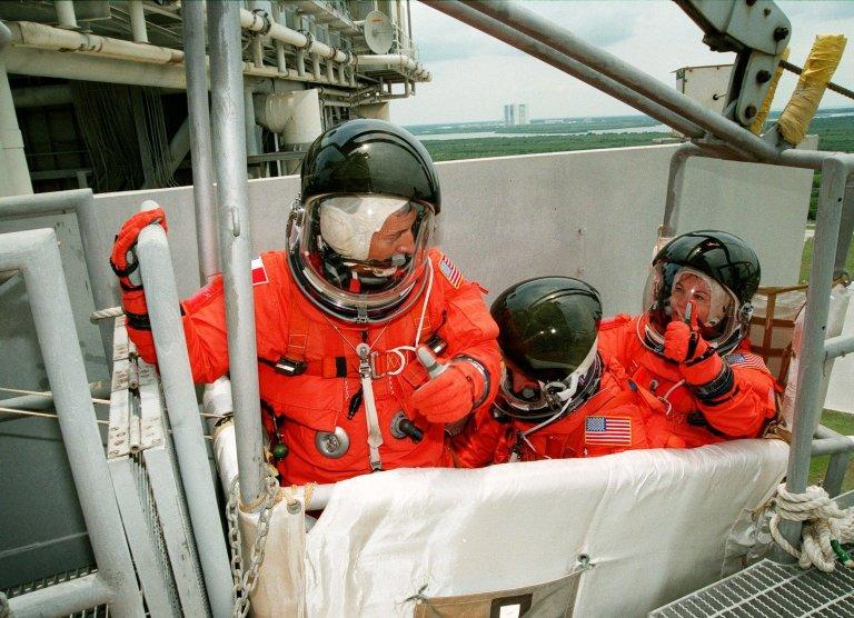 On Launch Pad 39B, (right) STS-93 Mission Specialist Catherine G. Coleman (Ph.D.) gives a thumbs up to Mission Specialist Michel Tognini of France (left) to pull the lever that will release the slidewire basket they are in. Also in the basket is Mission Specialist Steven A. Hawley (Ph.D.). The baskets are part of an emergency escape route for persons in the Shuttle and on the Rotating Service Structure. During the exercise, which is part of Terminal Countdown Demonstration Test (TCDT) activities, the basket is wired in place. The TCDT also includes a launch-day dress rehearsal culminating with a simulated main engine cut-off. Other crew members participating are Commander Eileen M. Collins and Pilot Jeffrey S. Ashby. Tognini represents the Centre National d'Etudes Spatiales (CNES). Collins is the first woman to serve as a Shuttle commander. The primary mission of STS-93 is the release of the Chandra X-ray Observatory, which will allow scientists from around the world to obtain unprecedented X-ray images of exotic environments in space to help understand the structure and evolution of the universe. The targeted launch date for STS-93 is no earlier than July 20 at 12:36 a.m. EDT from Launch Pad 39B