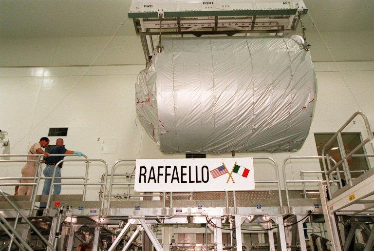 KENNEDY SPACE CENTER, FLA. -- The Multi-Purpose Logistics Module (MPLM) called Raffaello is suspended above a workstand in the Space Station Processing Facility (SSPF) where it will undergo testing. One of Italy's major contributions to the ISS program, the MPLM is a reusable logistics carrier and the primary delivery system used to resupply and return station cargo requiring a pressurized environment. Weighing nearly 4.5 tons, the Raffaello measures 21 feet long and 15 feet in diameter. Also inside the SSPF is the first Italian-built MPLM, Leonardo, also undergoing testing for its launch on mission STS-102 scheduled for June 29, 2000. Raffaello is scheduled to be launched on mission STS-100 on July 27, 2000