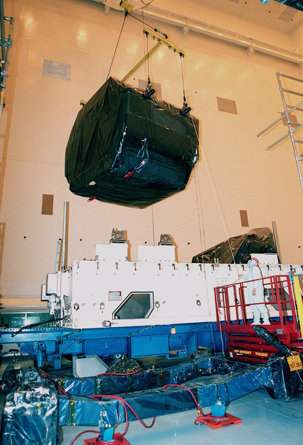 """In the Payload Hazardous Servicing Facility (PHSF), a crane lifts equipment for mission STS-103 out of its shipping container to move it to a workstand. The equipment is the first part of payload flight hardware for the third Hubble Space Telescope Servicing Mission (SM-3A). The hardware will undergo final testing and integration of payload elements in the PHSF. Mission STS-103 is a """"call-up"""" mission which is being planned due to the need to replace portions of the Hubble's pointing system, the gyros, which have begun to fail. Although Hubble is operating normally and conducting its scientific observations, only three of its six gyroscopes are working properly. The gyroscopes allow the telescope to point at stars, galaxies and planets. The STS-103 crew will not only replace gyroscopes, it will also replace a Fine Guidance Sensor and an older computer with a new enhanced model, an older data tape recorder with a solid state digital recorder, a failed spare transmitter with a new one, and degraded insulation on the telescope with new thermal insulation. The crew will also install a Battery Voltage/Temperature Improvement Kit to protect the spacecraft batteries from overcharging and overheating when the telescope goes into a safe mode. Launch of STS-103 is currently targeted for Oct. 14 but the date is under review"""