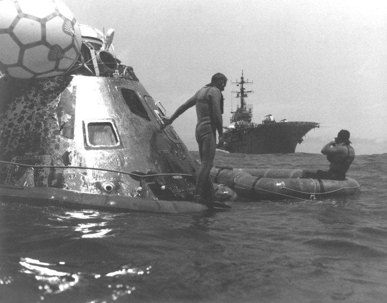 KENNEDY SPACE CENTER, FLA. -- Members of the Pacific Recovery Task Force secure the ASTP Apollo spacecraft as the USS New Orleans approaches to pick up the spacecraft and astronauts Thomas Stafford, Vance Brand and Donald Slayton. The Apollo splashed down in the Pacific Ocean, west of Hawaii, at 5:18 p.m., ending the nine-day joint US/USSR space mission.