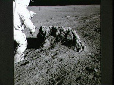 Astronaut Alan Shepard stands beside large boulder found by Apollo 14 crew