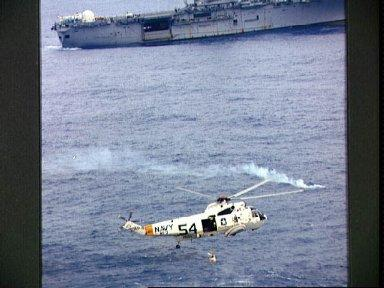 Apollo 9 crewman in rescue net being hoisted up to helicopter