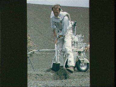 Astronaut Alan Shepard uses trenching tool during simulation of lunar surface