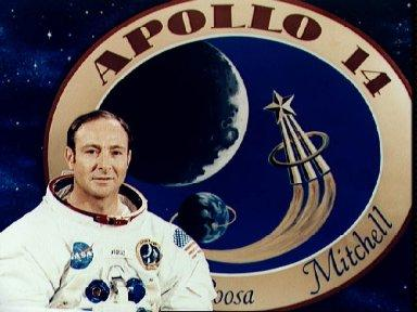 Astronaut Edgar D. Mitchell pictured in front of Apollo 14 insignia