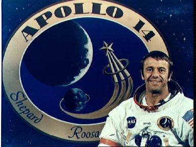 Astronaut Alan B. Shepard Jr. pictured in front of Apollo 14 insignia