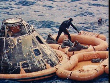 Apollo 14 astronauts assisted out of Command Module by Navy divers