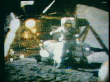 Astronaut David Scott watching hammer and feather fall to lunar surface