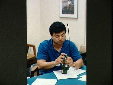 STS-65 Mission Specialist Chiao examines SARSAT PLB during bailout briefing