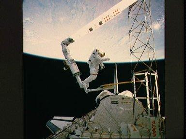 Astronaut Jerry Ross on RMS holds on to ACCESS device